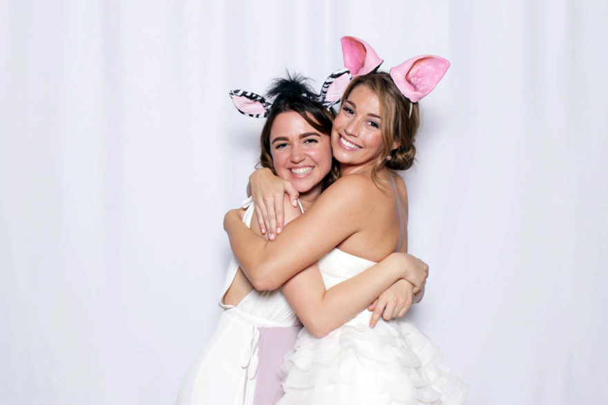 Bride & bridesmaid enjoying the photo booth at a wedding reception
