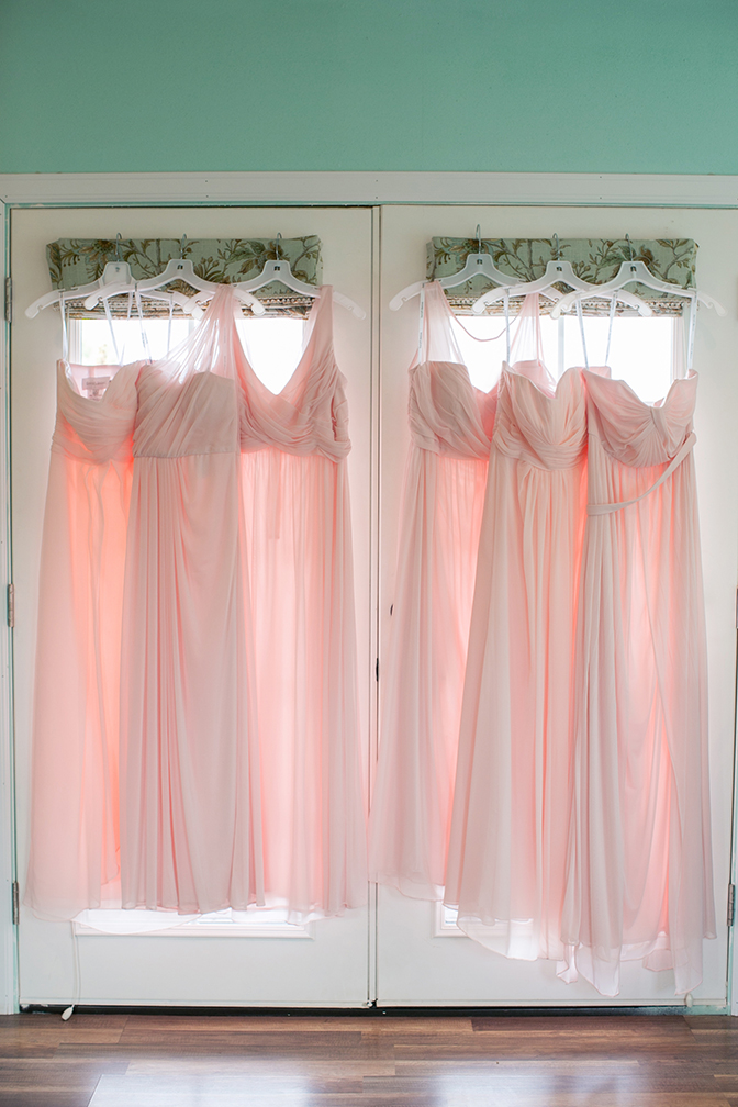 Light pink bridesmaids dresses hanging on door. Wedding photography inspiration and ideas.