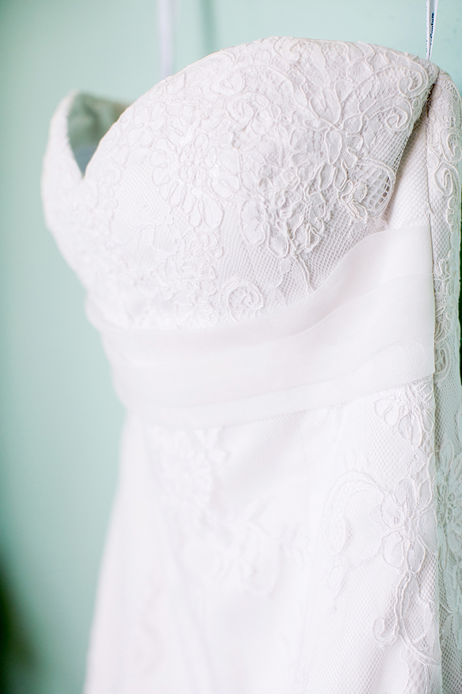 White strapless a-line wedding dress with lace overlay details.