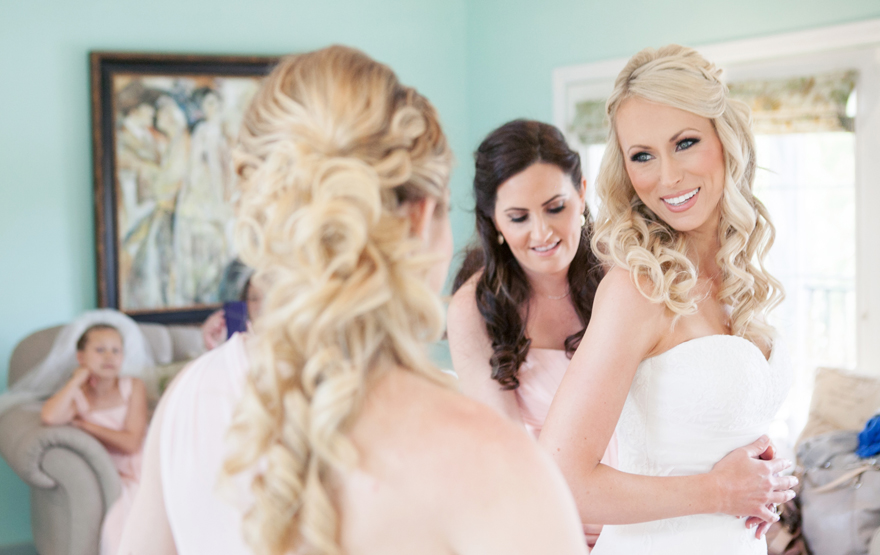 Bridesmaids helping beautiful blonde bride into her strapless wedding dress. Wedding inspiration.