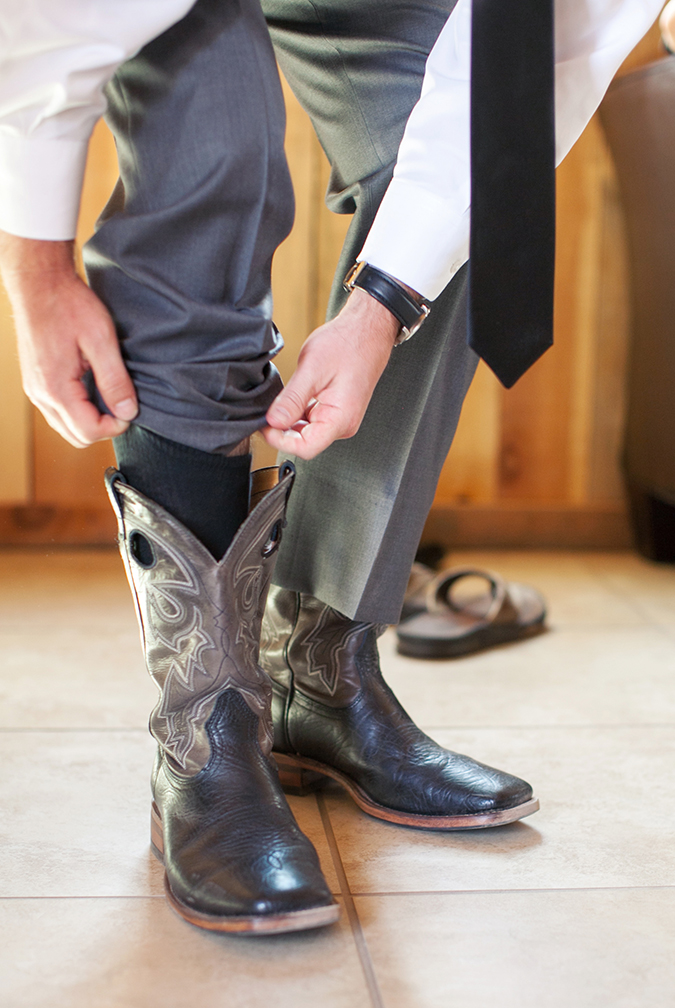 Groom puts on his cowboy boots for this country inspired wedding. Wedding groom photography ideas.