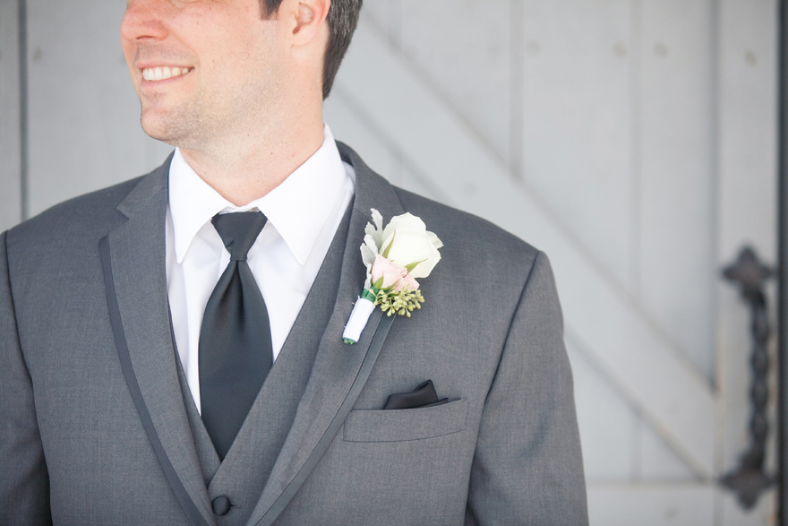 Groom portrait with white rose boutonniere and grey suit jacket. Wedding day photography.