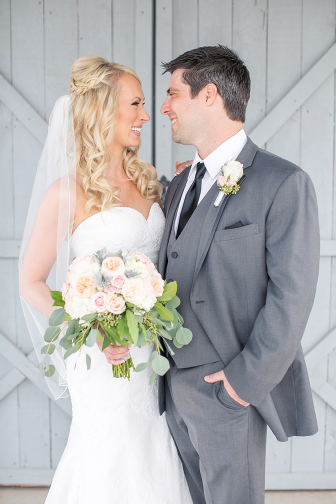 Blonde bride and groom smile at each other on their wedding day. Strapless a-line dress & grey suit.