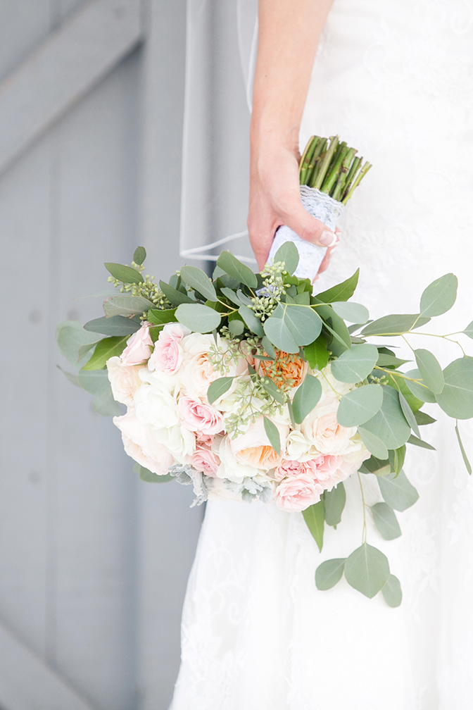 Bride holds beautiful white and light pink rose bouquet with french manicure on her wedding day.