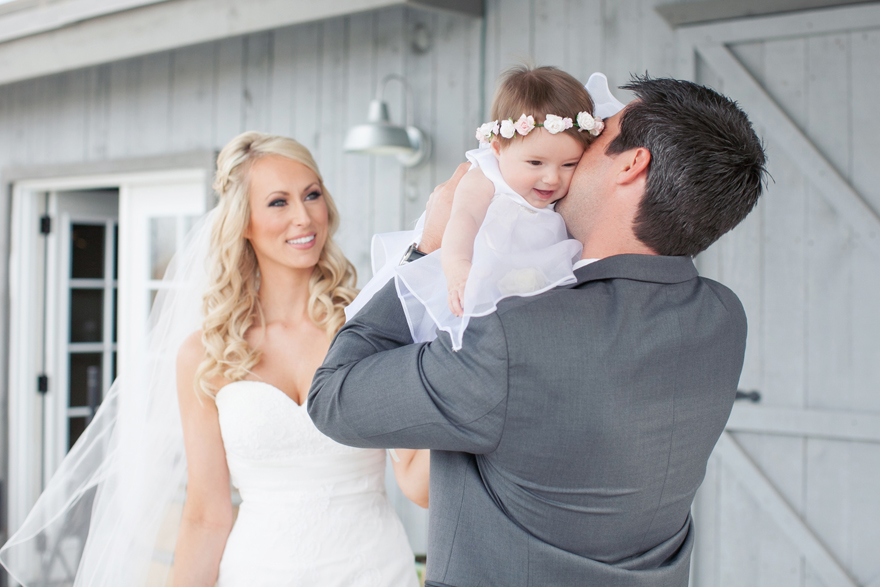 Bride, groom, and their baby daughter on their wedding day. Wedding day photo inspiration and ideas.
