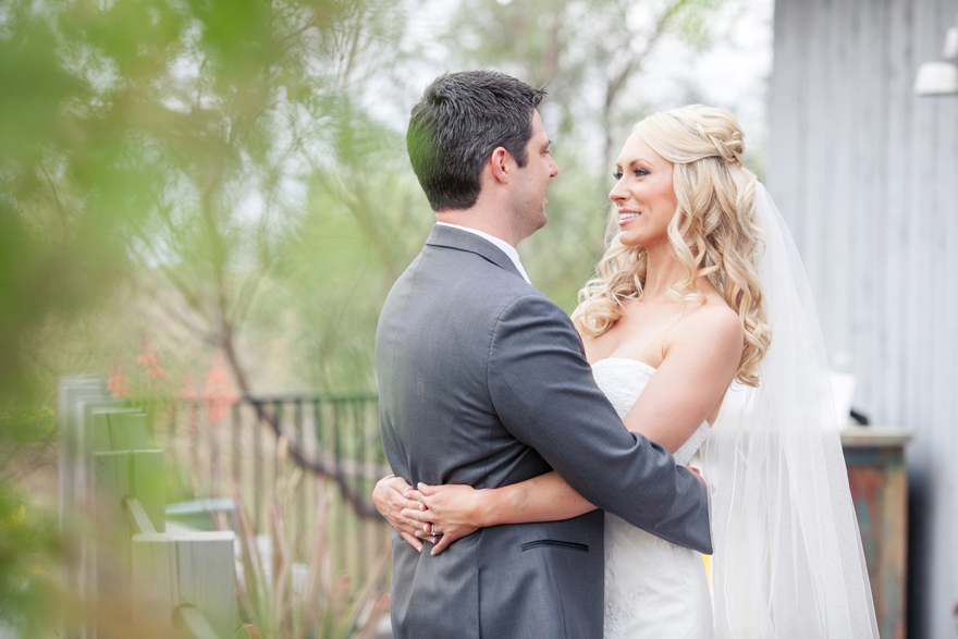 Blonde bride and groom hugging and smiling at each other romantically on their wedding day.