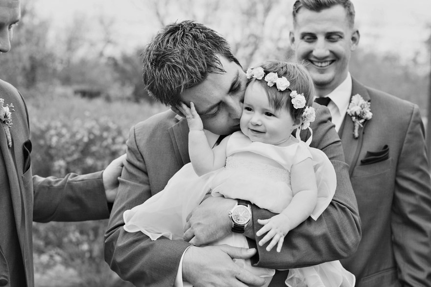 Groom kisses his baby daughter in adorable dress and floral crown. Wedding day photography ideas.