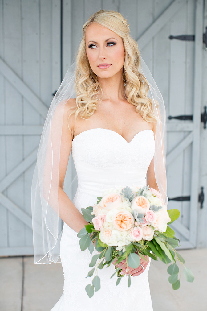 Gorgeous blonde bride in strapless a-line lace wedding dress with pink rose bouquet.