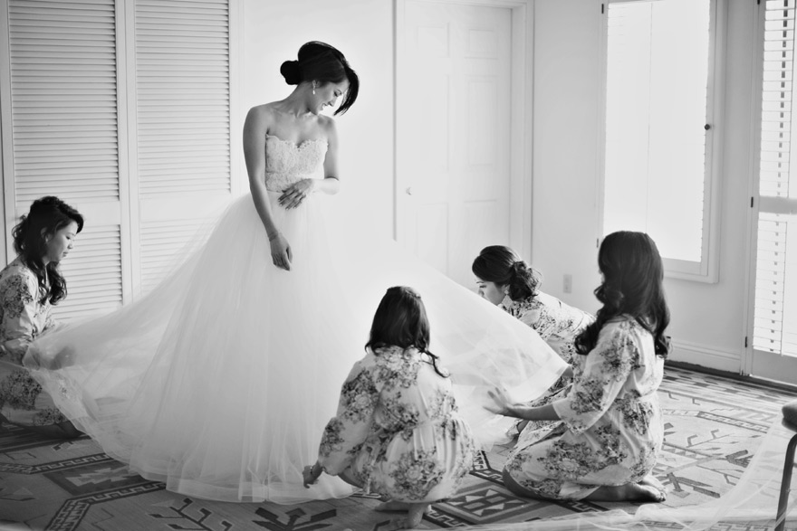 bridesmaids help a bride into her dress