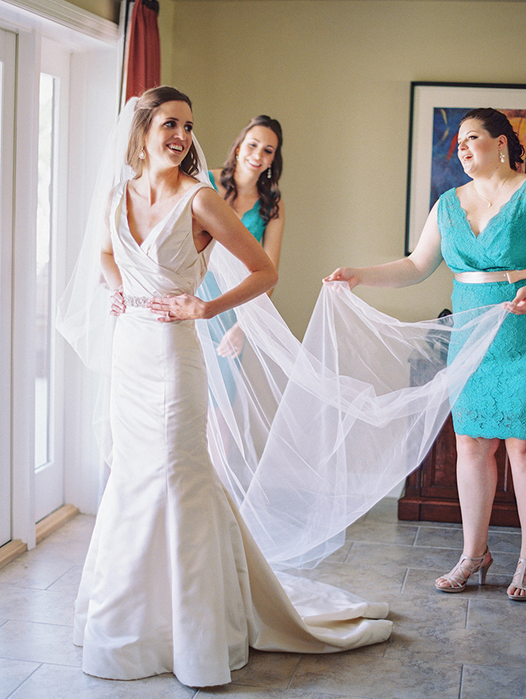 Bridesmaids help the bride put on her veil