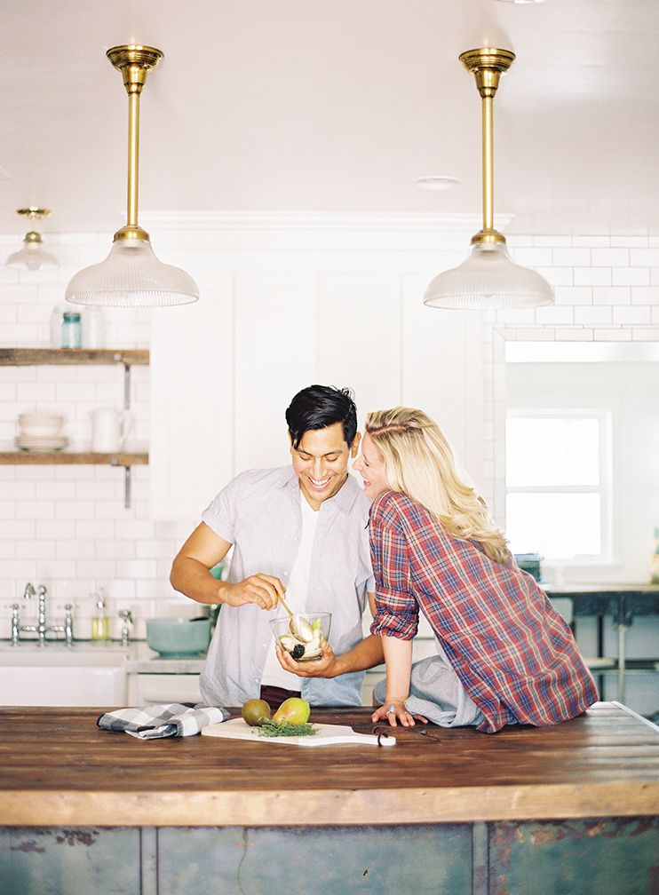 Engaged couple happily cooking together in rustic- modern kitchen