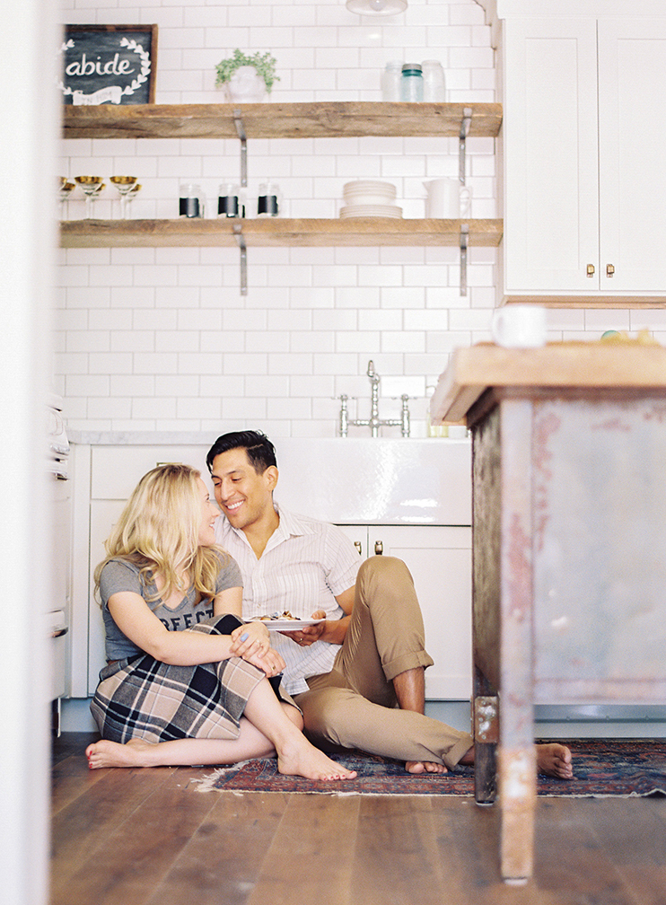 Couple sitting on wood flooring in modern rustic kitchen with white subway tile