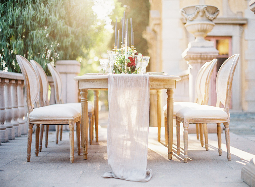 Romantic table with tall candles and a trailing linen runner